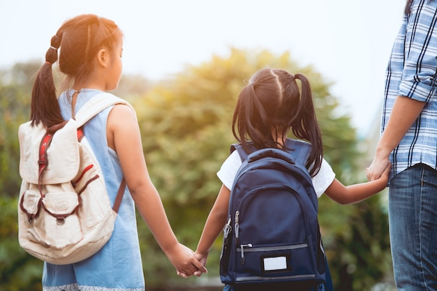 Asiatisches mutter- und tochterschülermädchen mit dem rucksack, der hand hält und zur schule geht