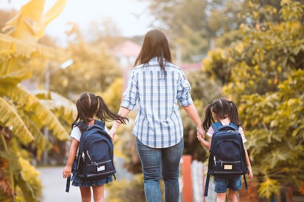 Asiatisches mutter- und tochterschülermädchen mit dem rucksack, der hand hält und zur schule zusammen geht