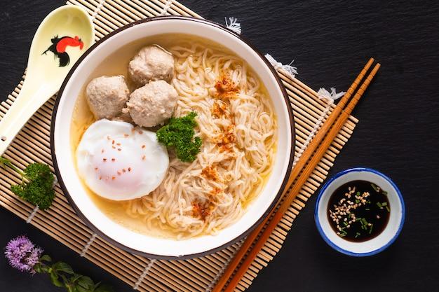 Asiatisches nahrungsmittelkonzept eiernudeln ramen asiatischer stil mit fleischbällchen auf mattschwarzem hintergrund des bambus mit kopienraum