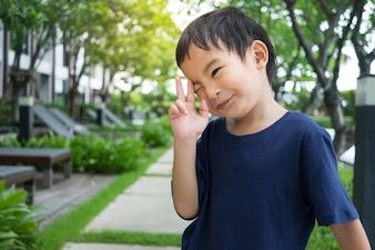 Asiatisches netter Junge tragen Marineblau-T-Shirt Lächeln und übergeben oben im grünen Naturhintergrund
