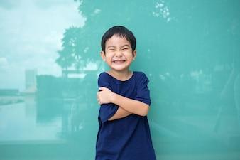 Asiatisches nettes Jungenlächeln und -spaß mit hellblauem Hintergrund