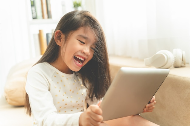 Asiatisches nettes kind, das spiele mit einer tablette spielt und beim auf sofa zu hause sitzen lächelt