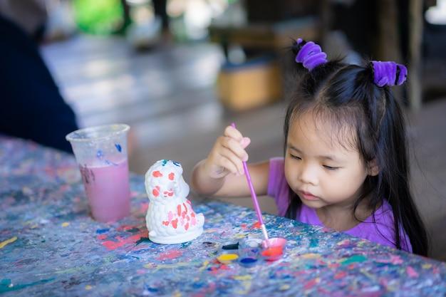Asiatisches nettes kleines mädchen, das spaß hat, auf stuckpuppe zu malen