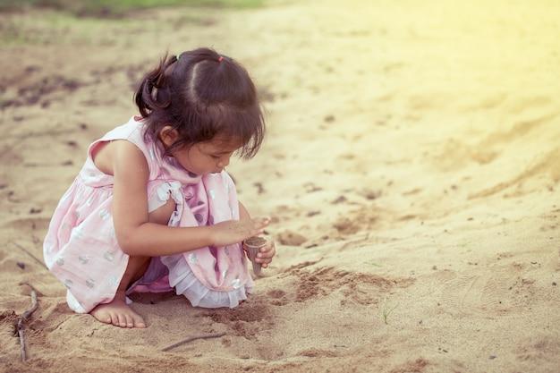 Asiatisches nettes kleines mädchen des kindes, das mit sand im spielplatz spielt