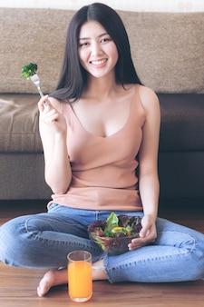 Asiatisches nettes mädchen der schönen schönheitsfrau des lebensstils fühlen sich glücklich genießen, frischen salat des diätlebensmittels und orangensaft für gute gesundheit morgens zu essen