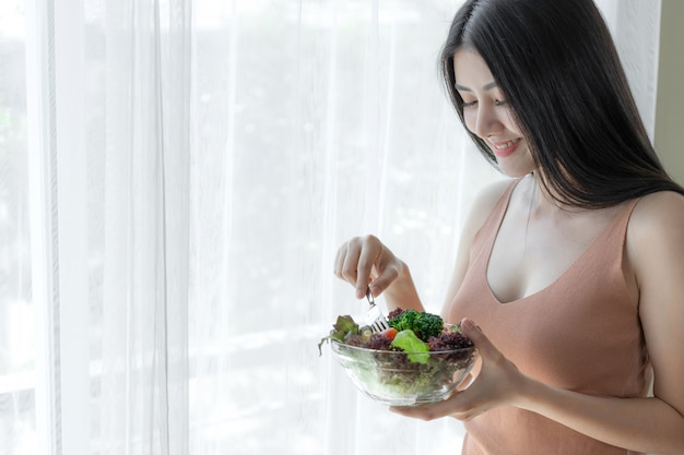 Asiatisches nettes mädchen der schönen schönheitsfrau fühlen sich glücklich, frischen salat des diätlebensmittels für gute gesundheit morgens essend