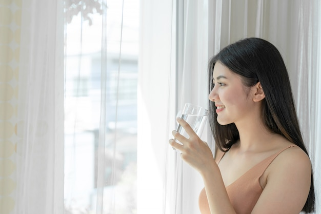 Asiatisches nettes mädchen der schönen schönheitsfrau fühlen sich glücklich, sauberes getränkwasser für gute gesundheit morgens trinkend