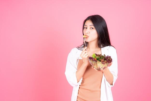 Asiatisches nettes mädchen der schönheitsfrau fühlen sich glücklich, frischen salat des diätlebensmittels für gute gesundheit auf rosa hintergrund essend