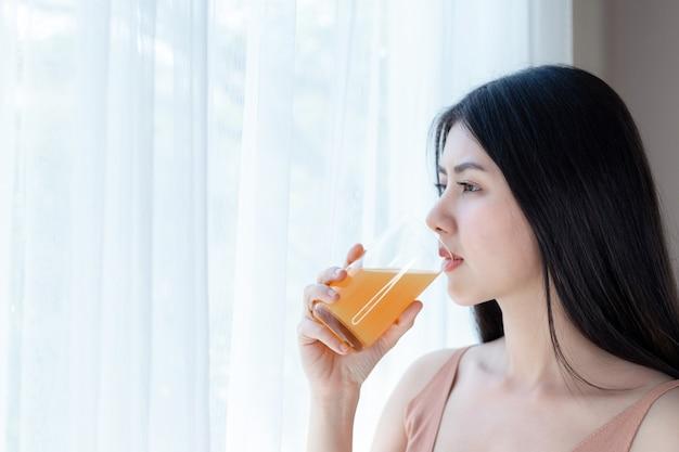 Asiatisches nettes mädchengefühl der schönen schönheitsfrau glücklich, orangensaft für gute gesundheit morgens trinkend