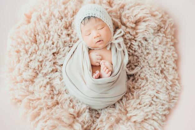 Asiatisches neugeborenes baby mit dem strickmützeschlafen