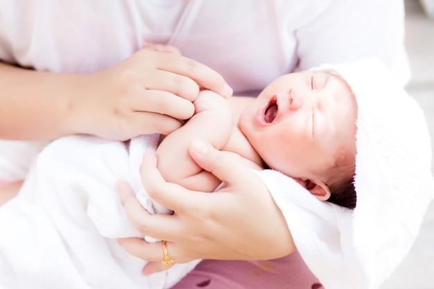 Asiatisches neugeborenes im arm der mutter, nachdem ein bad gebadet worden ist