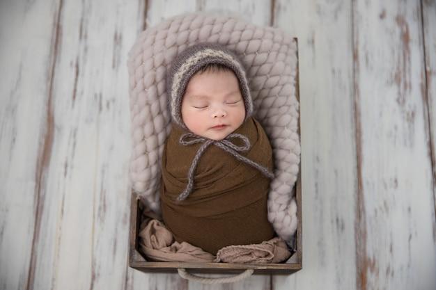 Asiatisches neugeborenes im braunen wickel mit kapuze schlaf in einer kiste