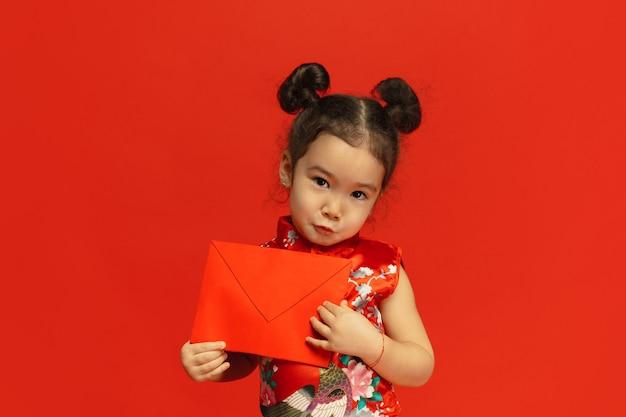 Asiatisches niedliches kleines mädchen lokalisiert auf roter wand in traditioneller kleidung