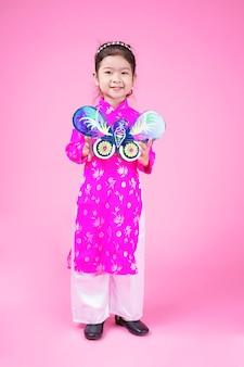 Asiatisches niedliches kleines mädchenkind mit reizendem ausdruck im kleinen hintergrund
