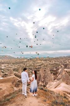 Asiatisches paar, das bunte heißluftballons beobachtet, die über das tal bei kappadokien, türkei fliegen diese romantische zeit der liebe