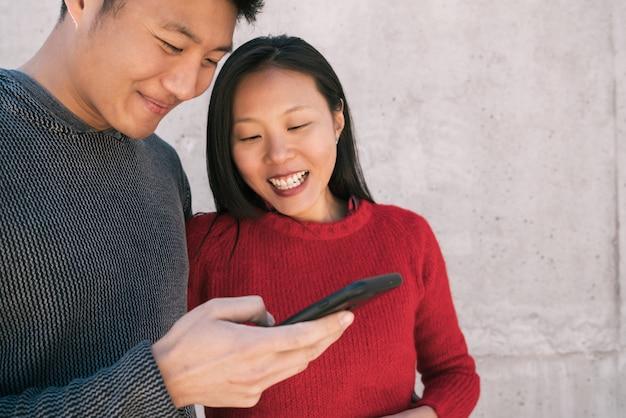 Asiatisches paar, das das handy betrachtet.
