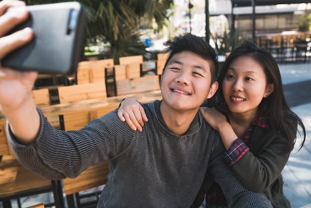 Asiatisches paar, das ein selfie mit handy nimmt.