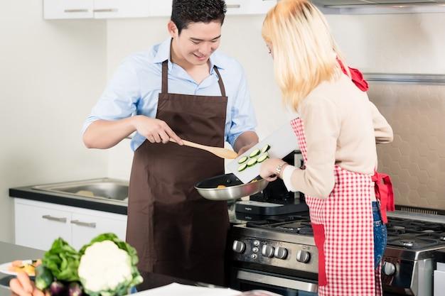 Asiatisches paar, das gemüse in der pfanne kocht