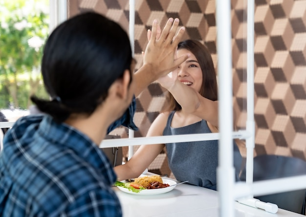 Asiatisches paar, das im neuen normalen restaurant auswärts isst