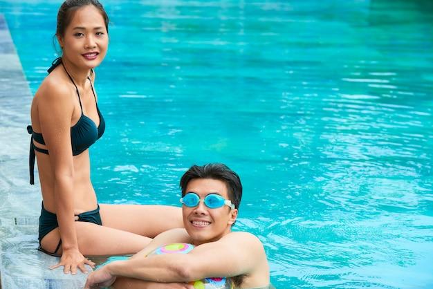 Asiatisches paar, das im schwimmbad ruht