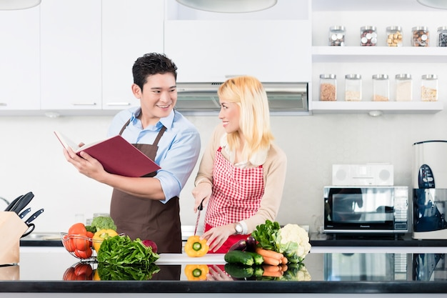 Asiatisches paar, das in der stilvollen und modernen küche kocht