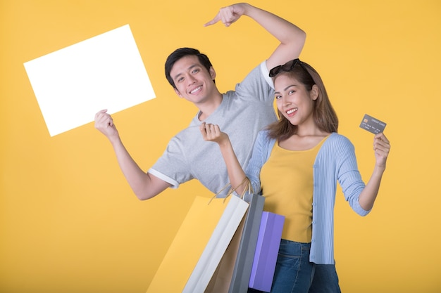 Asiatisches paar, das leere plakatwand mit kreditkarte und einkaufstüten isoliert auf gelbem hintergrund hält