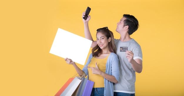 Asiatisches paar, das leere plakatwand mit kreditkarte und einkaufstüten und smartphone isoliert auf gelbem hintergrund hält