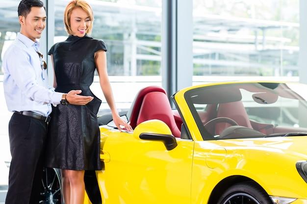 Asiatisches paar, das luxus-sportwagen im autohaus wählt, der einen roadster betrachtet