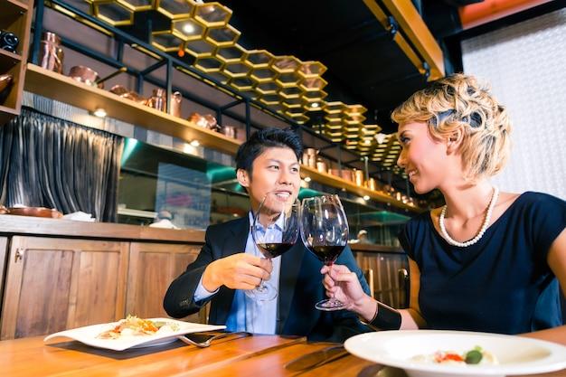 Asiatisches paar, das mit rotwein röstet