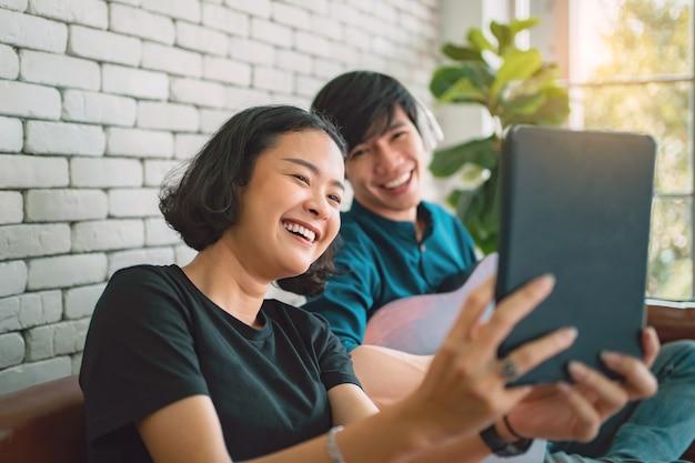Asiatisches paar, das mit selbstaufnahme lächelt und auf sofa im wohnzimmer sitzt