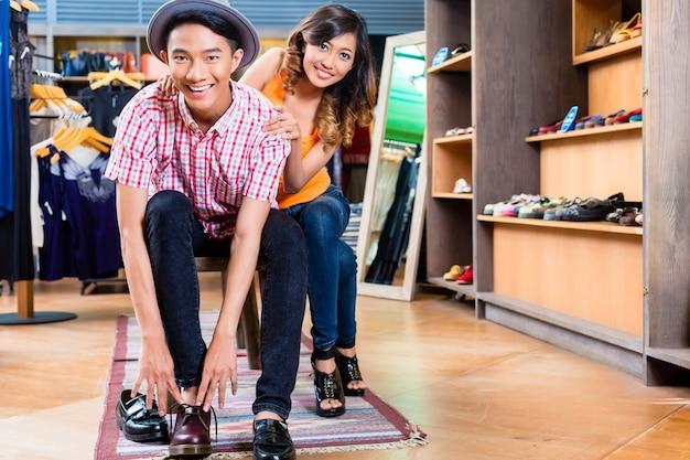 Asiatisches paar, das schuhe im laden oder im laden kauft
