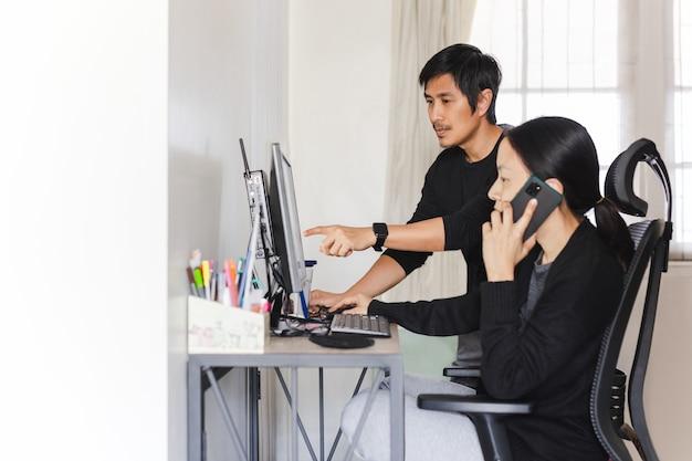 Asiatisches paar, das zu hause am computer zusammenarbeitet.