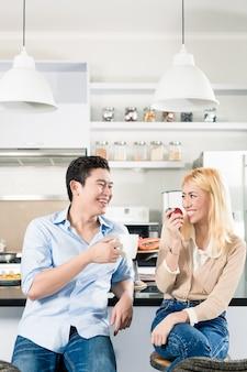 Asiatisches paar, das zusammen in der modernen wohnung frühstückt