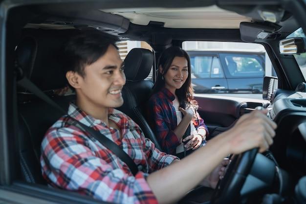 Asiatisches paar, das zusammen mit dem auto fährt