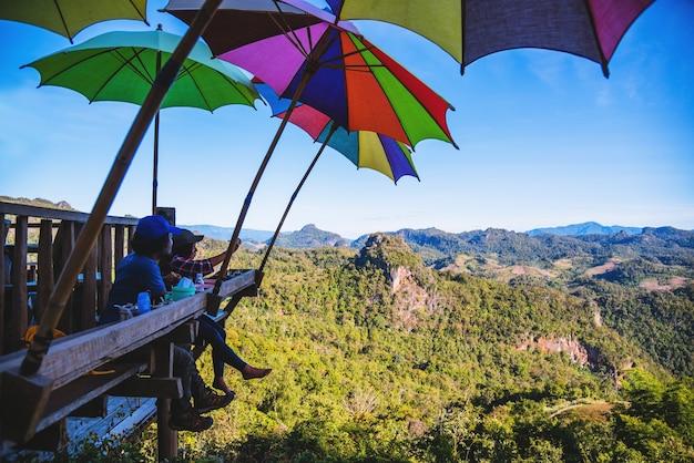 Asiatisches paar der touristen, das sitzt, isst nudeln auf der holzplattform und blickt auf die malerische aussicht auf die wunderschönen naturberge bei ban jabo, mae hong son, thialand.