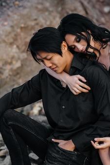 Asiatisches paar in den umarmungen, die auf den felsen sitzen. liebesgeschichte