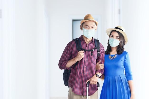 Asiatisches paar in der gesichtsmaske mit koffertasche und rucksack auf dem krankenhaus. ärztliche untersuchung vor reiseantritt
