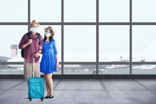 Asiatisches paar in der gesichtsmaske mit koffertasche und rucksack, die auf dem flughafenterminal stehen. reisen in der neuen normalität