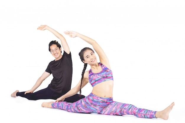 Asiatisches paar macht yoga über weißem hintergrund