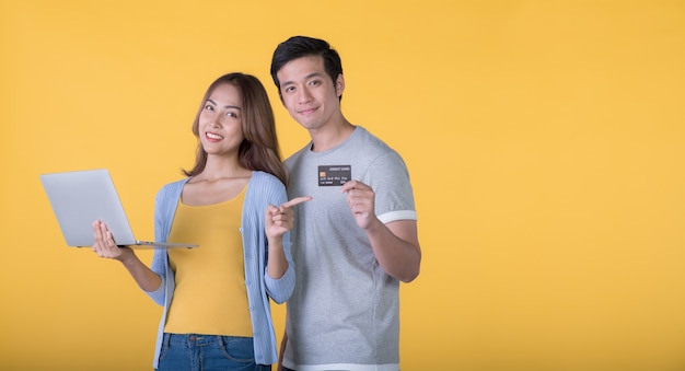 Asiatisches paar mit kreditkarte und laptop beim betrachten einer kamera auf gelbem hintergrund yellow