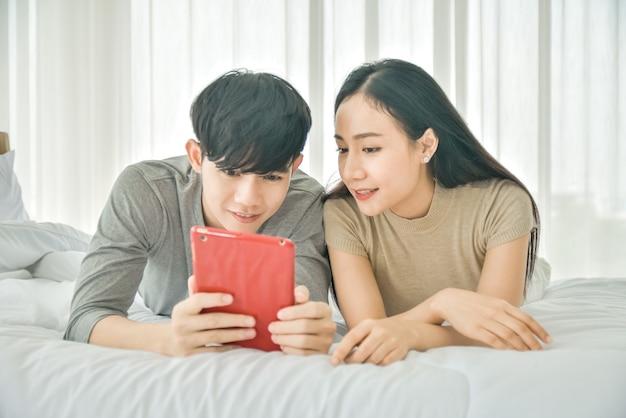 Asiatisches paar mit tablette glücklich auf schlafzimmer