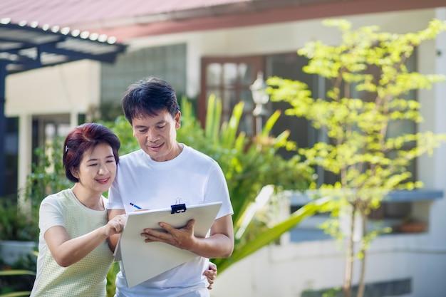 Asiatisches paar mittleren alters, das gartenplan zusammen im hinterhof spricht und entwirft.