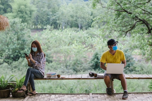 Asiatisches paar soziale distanzierung und tragen von schutzmasken, coronavirus covid-19 krankheitsschutz. gespräch aus sicherer entfernung. einschränkung der sozialisation.