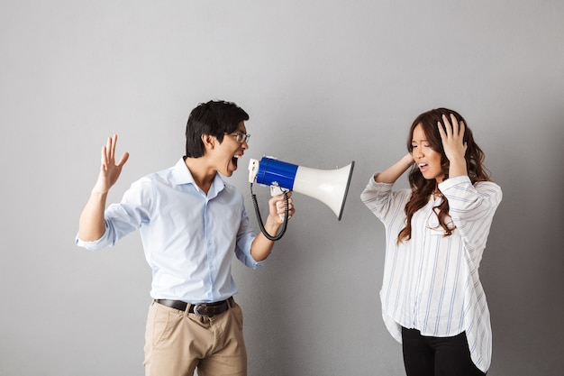 Asiatisches paar stehend, mann, der in einem lautsprecher schreit
