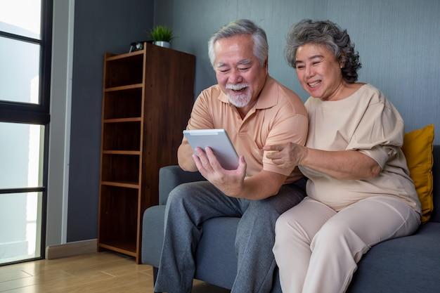 Asiatisches paar von senioren, die lächeln und dieselbe tablette auf dem sofa zu hause betrachten