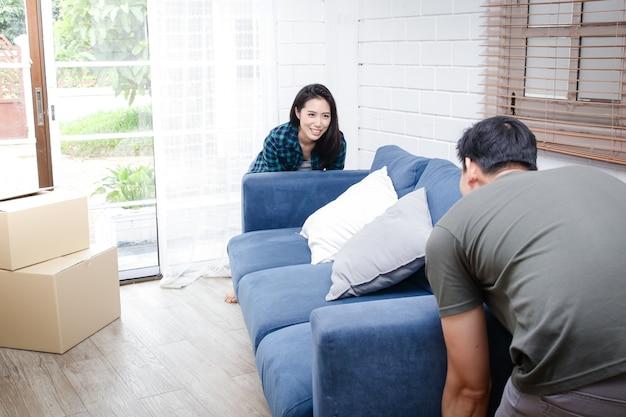 Asiatisches paar zieht in ein neues zuhause. helfen sie sich gegenseitig, das sofa ins wohnzimmer zu bringen.