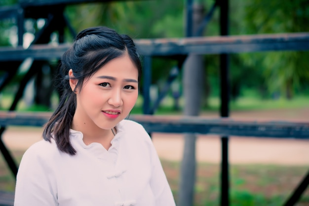 Asiatisches porträt der nahaufnahme eines schönen mädchens in einem weißen kleid im sommer.