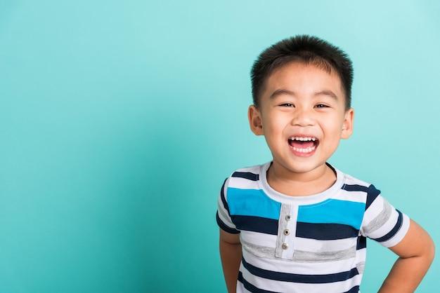 Asiatisches porträt des glücklichen gesichtes des kleinen jungen, den er lachend lächelt und zur kamera schaut