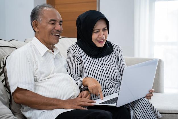 Asiatisches reifes paar, das eine moderne technologie durch einen laptop genießt