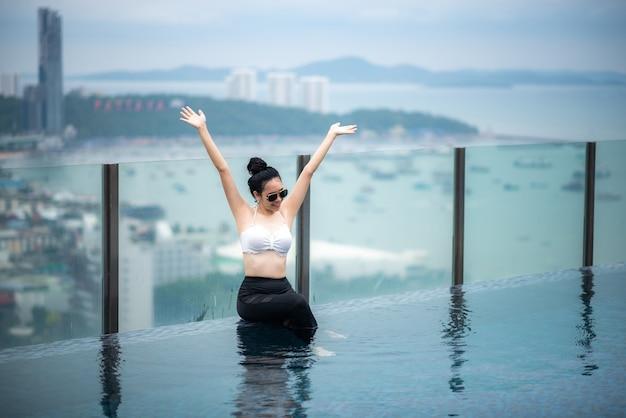 Asiatisches reisekonzept. junge frau, die den blick auf den stadthimmel vom pool auf dem dach des hotels genießt, schöner mädchenlebensstil im freien in der urlaubszeit